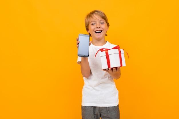 Glücklicher junge hält einen kasten und zeigt den telefonschirm