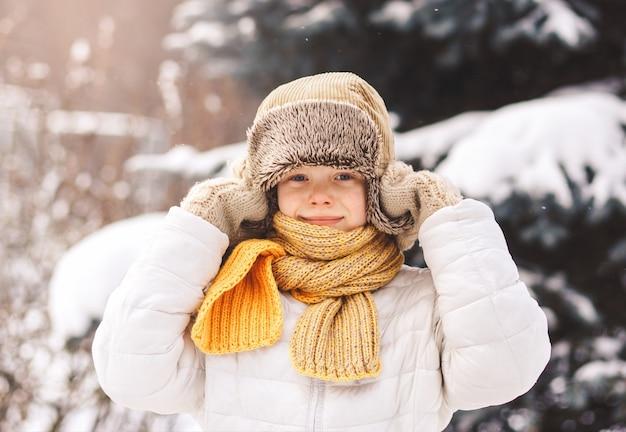 Glücklicher junge im flauschigen winterhut draußen