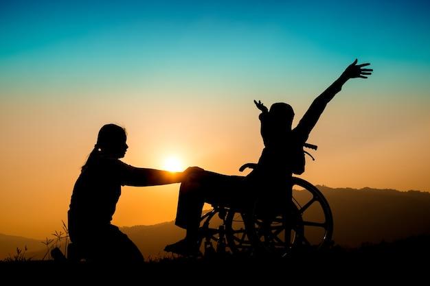 Glücklicher junge im rollstuhl und in der schwester auf sonnenuntergang. glückliches behindertes kinderkonzept