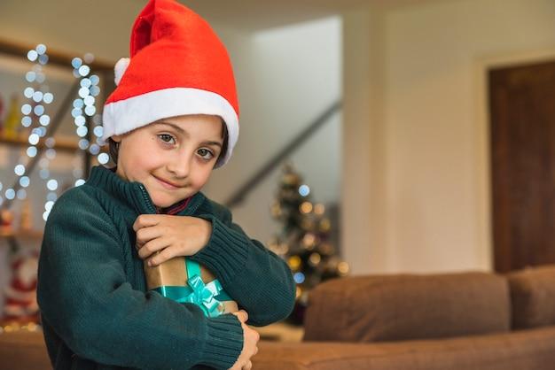 Glücklicher junge im weihnachtshut mit präsentkarton