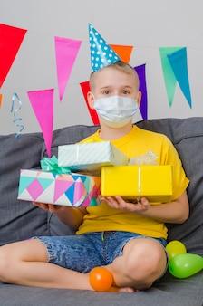 Glücklicher junge in der gesichtsmaske der medizin mit geschenken in der hand feiert geburtstag