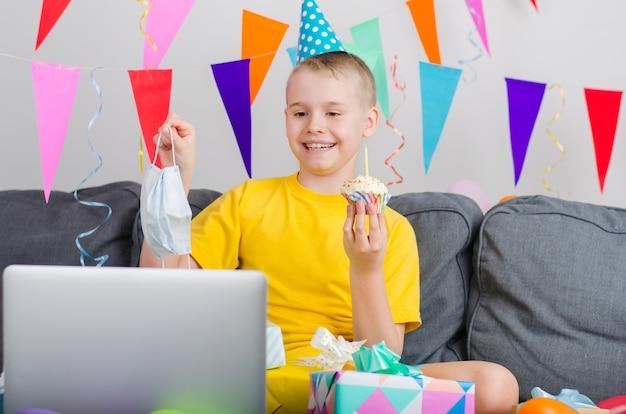Glücklicher junge in der medizingesichtsmaske feiert geburtstag durch videoanruf zum laptop