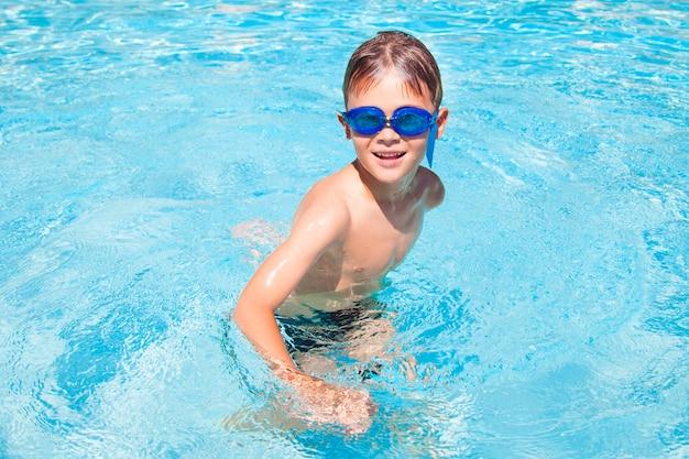 Glücklicher junge in einem schwimmbad. netter kleiner junge, der spaß in einem schwimmbad hat. draußen. sportliche aktivitäten für kinder.