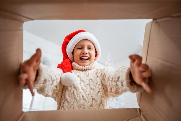 Glücklicher junge in einer gestrickten und weihnachtsmannmütze schaut in die schachtel