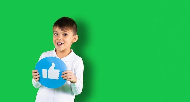 Glücklicher junge lächelt und zeigt rundes banner mit ähnlichem zeichen an