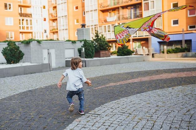 Glücklicher junge mit einem drachen, der auf den straßen spielt