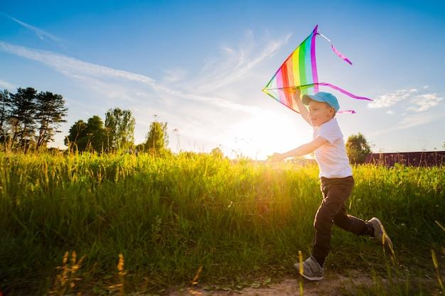 Glücklicher junge mit einem drachen, der in eine wiese im sommer in der natur läuft.
