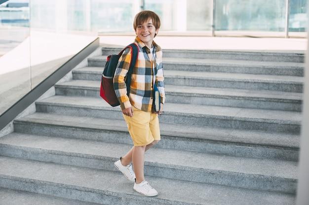 Glücklicher junge mit einem rucksack und einem buch geht zur schule