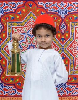 Glücklicher junge mit fez und laterne, die ramadan feiern