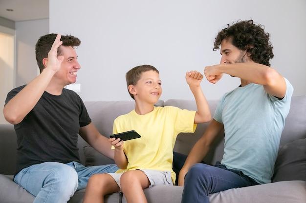 Glücklicher junge mit handy, das fauststoßgeste mit zwei fröhlichen vätern macht. väter und sohn spielen zusammen auf dem handy. konzept der familie zu hause und der schwulen eltern
