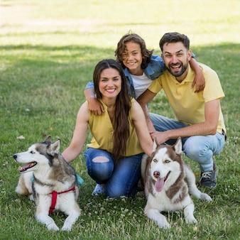 Glücklicher junge mit hunden und eltern, die zusammen am park aufwerfen