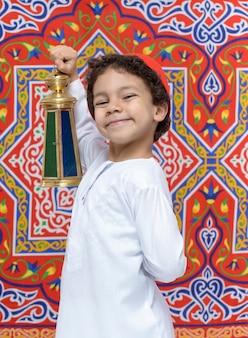 Glücklicher junge mit laterne, die ramadan feiert