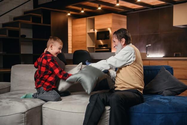 Glücklicher junge mit lustigem modernen opa, der mit kissen kämpft, die spaß zusammen sitzen auf bequemer couch zu hause haben.