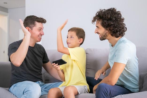 Glücklicher junge mit smartphone, das hohe fünf bis zwei fröhliche väter gibt. väter und sohn spielen zusammen auf dem handy. konzept der familie zu hause und der schwulen eltern