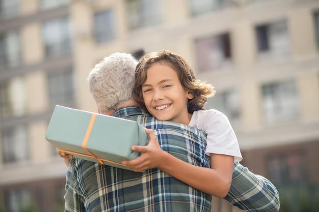 Glücklicher junge. netter junge, der ein geschenk hält und seinen vater umarmt