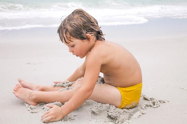 Glücklicher junge spielt mit sand am strand. aktivitäten für kinder am strand.