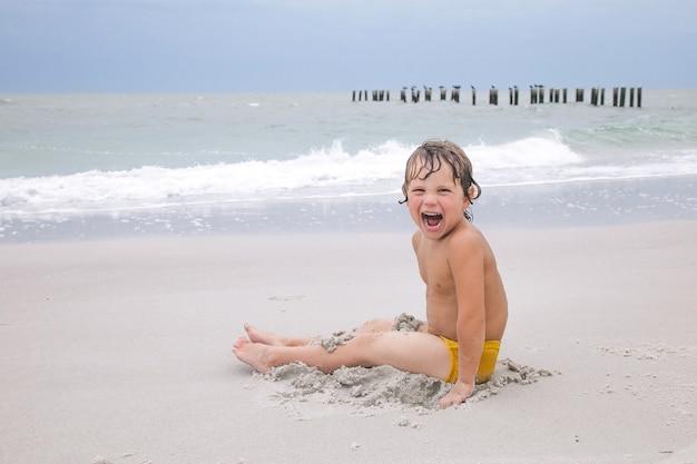 Glücklicher junge spielt mit sand am strand. kind, das im ozean spielt und schwimmt. ferien. aktivitäten für kinder am strand. spaß und freude