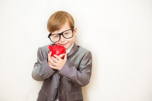 Glücklicher junge steht in einem modischen anzug mit einem sparschwein in seinen händen. geschäftskonzept für erfolg, kreativität und innovation