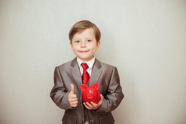 Glücklicher junge steht in einem modischen anzug mit einem sparschwein in seinen händen