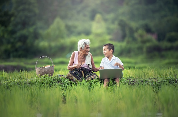 Glücklicher junge und großmutter, die draußen einen laptop verwendet