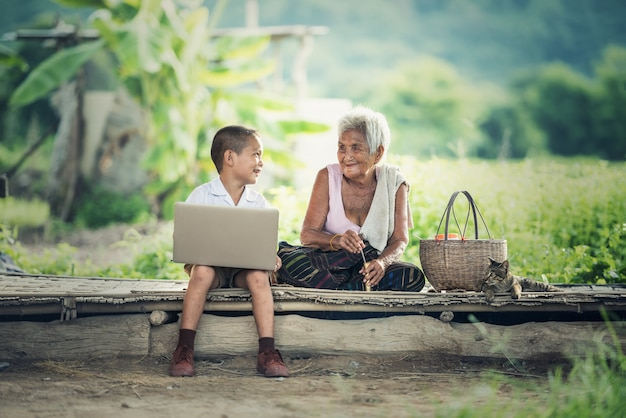 Glücklicher junge und großmutter, die laptop verwendet