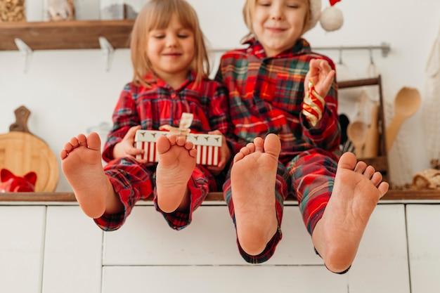 Glücklicher junge und mädchen, die weihnachtsgeschenk halten