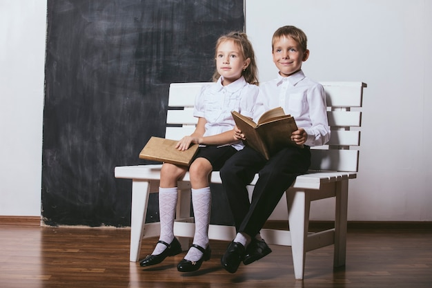 Glücklicher junge und mädchen von der grundschulklasse auf der bank lesen bücher auf dem hintergrund des schiefers