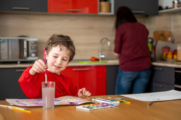 Glücklicher junge zeichnet malerei auf küche mit mutter