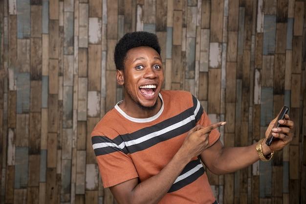 Glücklicher junger afrikaner, der ein handy hält