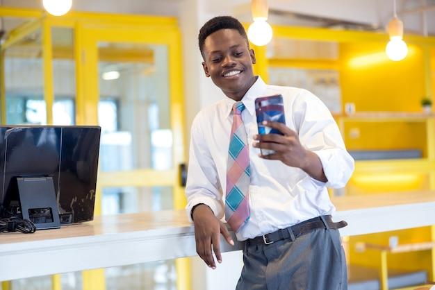 Glücklicher junger afrikaner, der lächelt, während er drinnen ein selfie auf dem handy macht