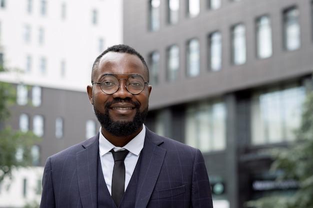 Glücklicher junger afrikanischer geschäftsmann, der in der städtischen umgebung steht