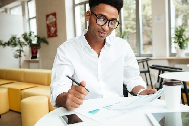 Glücklicher junger afrikanischer mann, der coworking sitzt