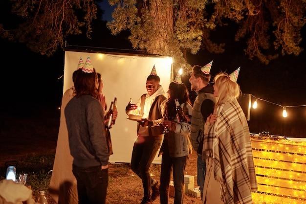 Glücklicher junger afrikanischer mann, der hand durch kerzen auf geburtstagstorte hält, während unter freunden in kappen steht, die mit flaschen bier rösten