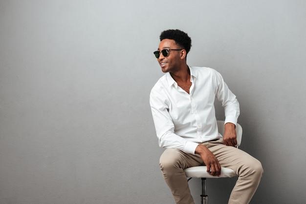 Glücklicher junger afrikanischer mann, der in einem stuhl sitzt