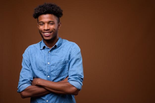 Glücklicher junger afrikanischer mann, der lächelt und kamera betrachtet