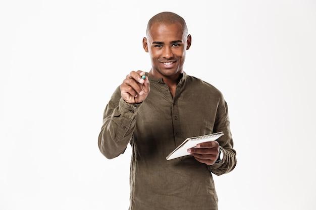 Glücklicher junger afrikanischer mann, der notizen schreibt