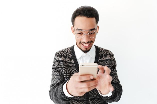 Glücklicher junger afrikanischer mann, der per telefon plaudert.