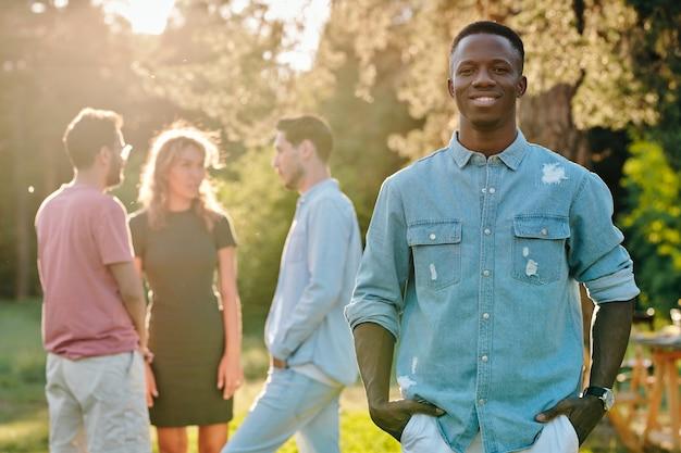 Glücklicher junger afrikanischer mann im jeanshemd, der im park auf gruppe seiner interkulturellen freunde steht, die ihre ideen des weggehens diskutieren