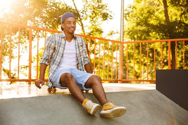 Glücklicher junger afrikanischer mann mit skateboard