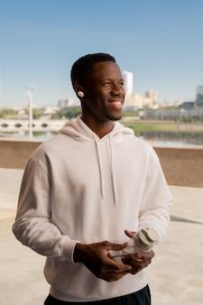 Glücklicher junger afrikanischer sportler mit zahnigem lächeln, das flasche wasser hält, während ruhe nach dem training im freien und musik hören hat