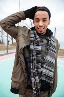 Glücklicher junger afroamerikaner junger mann, der draußen steht