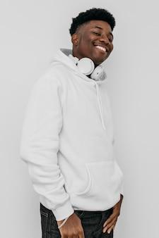 Glücklicher junger afroamerikanermann, der einen weißen kapuzenpulli trägt