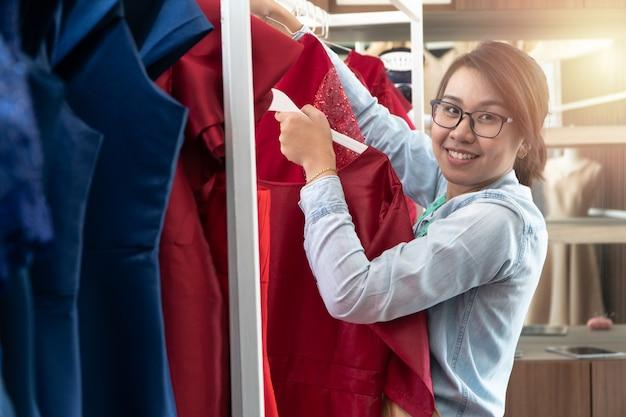 Glücklicher junger asiatindamenschneiderinmodedesigner überprüft auf fertigstellung für einen anzug und ein kleid in einem ausstellungsraum.