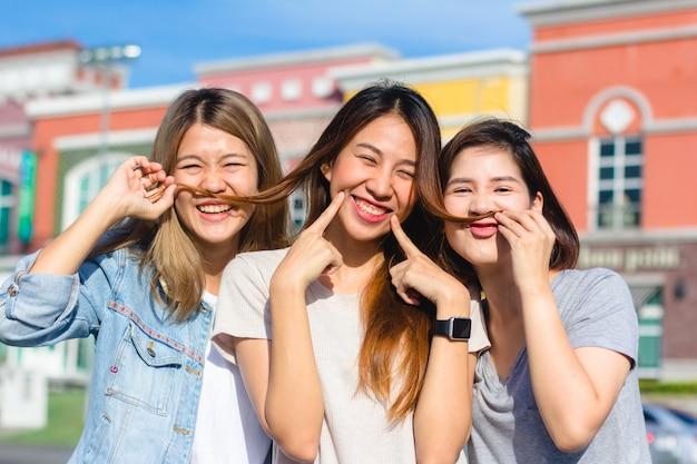 Glücklicher junger asiatinnengruppenstadtlebensstil, der spielt und sich unterhält