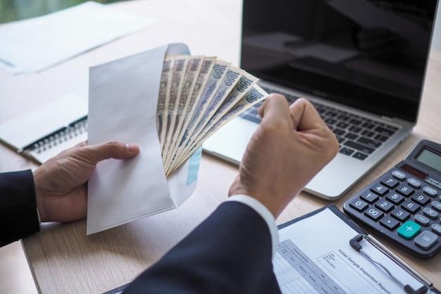 Glücklicher junger asiatischer angestellter geschäftsmann, der geldbonuskarte im papierumschlag zur erhöhung des gehalts oder der beförderung neuer position im amt, bonus hält
