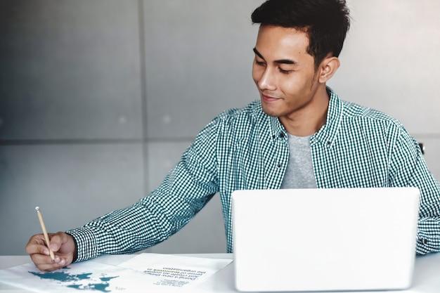 Glücklicher junger asiatischer geschäftsmann, der an computer-laptop in seinem arbeitsplatz arbeitet