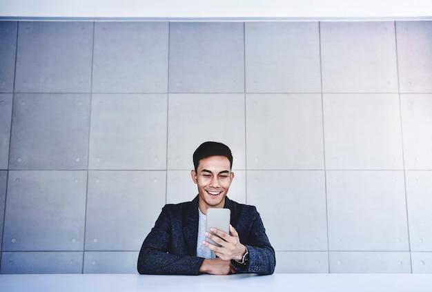 Glücklicher junger asiatischer geschäftsmann, der an smartphone arbeitet. weitwinkelaufnahme