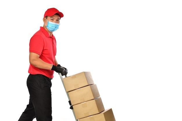 Glücklicher junger asiatischer lieferbote in der roten uniform, in der medizinischen gesichtsmaske, in den schutzhandschuhen, die einen handwagen mit den isolierten kisten drücken