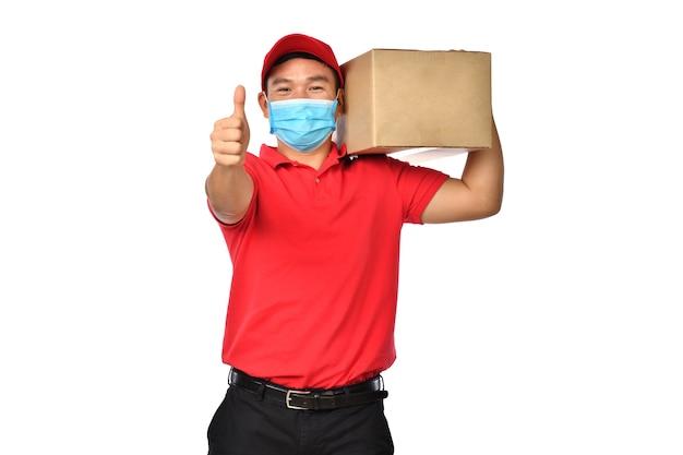 Glücklicher junger asiatischer lieferbote in der roten uniform, medizinische gesichtsmaske mit paketkarton