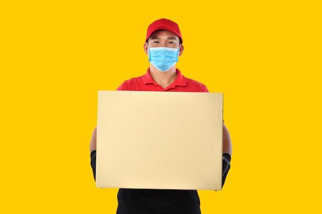 Glücklicher junger asiatischer lieferbote in der roten uniform, medizinische gesichtsmaske, schutzhandschuhe tragen pappkarton in den händen auf gelber wand. zusteller geben paketversand. während des covid-19-ausbruchs